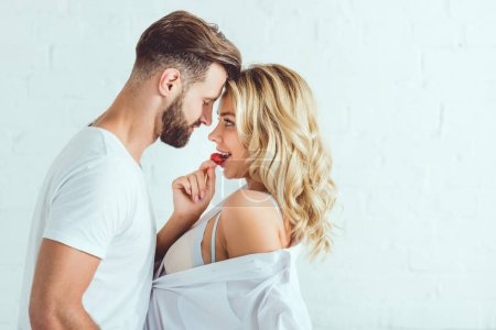 Photo for Handsome young man hugging beautiful girlfriend tasting strawberry - Royalty Free Image