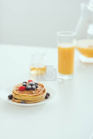 Photo for Selective focus of plate with tasty pancakes and berries near glass and jug of orange juice and jar with honey on white table - Royalty Free Image