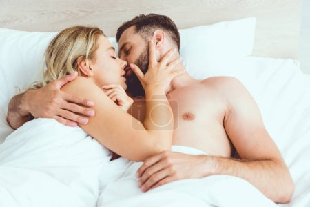 Foto de Happy young couple hugging and kissing with closed eyes while lying in bed - Imagen libre de derechos