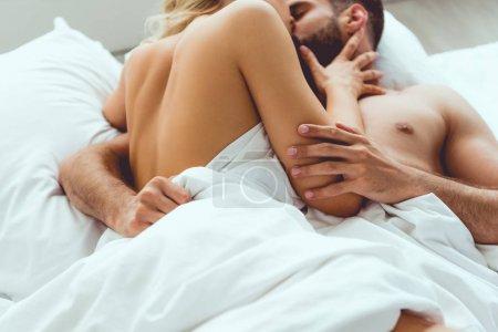 Foto de Partial view of young couple hugging and kissing while lying in bed - Imagen libre de derechos