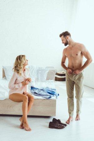 Photo pour Heureux jeune couple regardant l'autre tout en s'habillant dans la chambre - image libre de droit