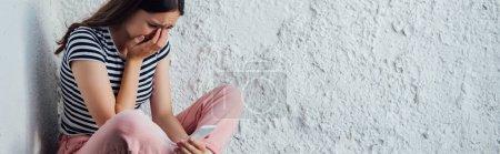 Photo pour Tir panoramique de la fille pleurant triste retenant le smartphone - image libre de droit