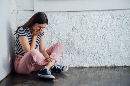 Photo pour Fille triste pleurante dans le pantalon rose s'asseyant près du mur et retenant le smartphone - image libre de droit