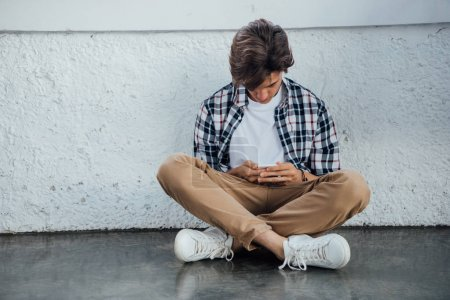 Photo for Front view of teenager sitting with crossed legs and using smartphone - Royalty Free Image
