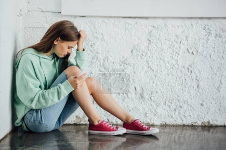 Photo for Sad girl sitting near textured wall and holding smartphone - Royalty Free Image