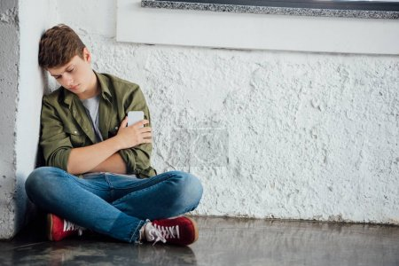 Photo for Sad teenager sitting with crossed legs and holding smartphone - Royalty Free Image
