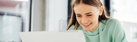 Photo pour Plan panoramique de fille souriante en sweat à capuche décontracté assis à table et à l'aide d'un ordinateur portable - image libre de droit