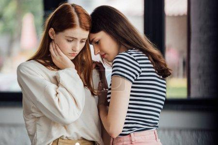 Photo pour Deux amis tristes dans des tenues décontractées regardant vers le bas - image libre de droit