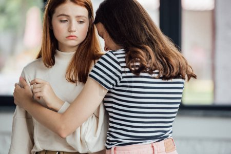 Photo for Teen girl in striped t-shirt embracing and supporting sad friend - Royalty Free Image