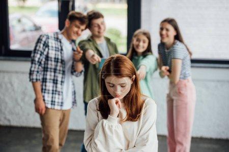 Foto de Enfoque selectivo del grupo de adolescentes intimidando chica triste - Imagen libre de derechos