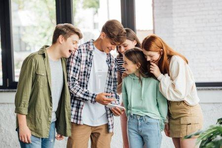 Foto de Grupo de amigos felices riendo mientras se utiliza el teléfono inteligente - Imagen libre de derechos