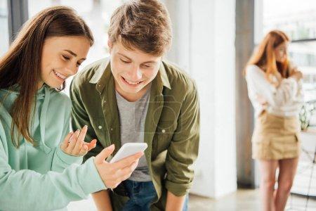 Photo pour Deux amis heureux souriant tout en utilisant le smartphone à l'école - image libre de droit