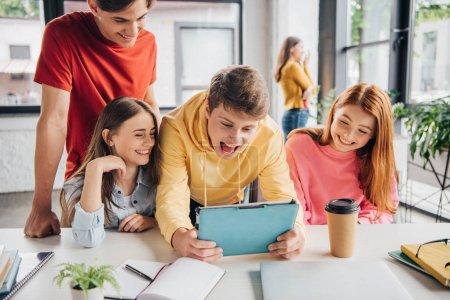 Foto de Grupo de escolares sonrientes usando la tableta digital en el aula - Imagen libre de derechos