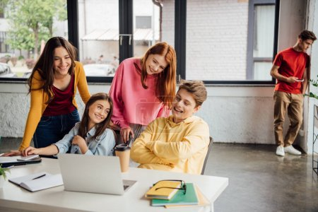 Photo for Smiling teenagers sitting at desk with laptop and notebooks in classroom - Royalty Free Image