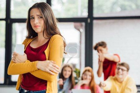 Foto de Grupo de escolares intimidando chica triste con teléfono inteligente - Imagen libre de derechos