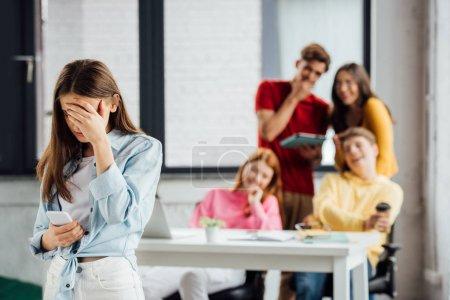 Photo pour Groupe d'écoliers riant de fille triste avec smartphone - image libre de droit