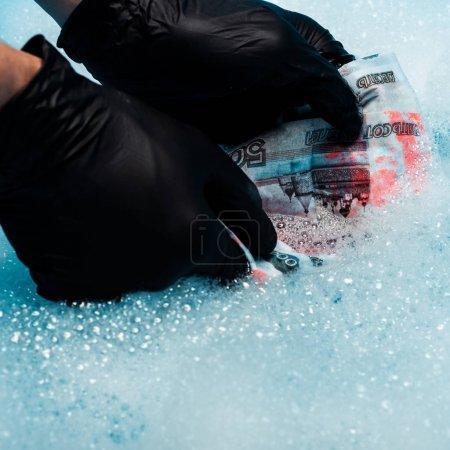 Photo pour Gros plan de l'homme en gants de caoutchouc noir laver l'argent russe dans des bulles de savon - image libre de droit