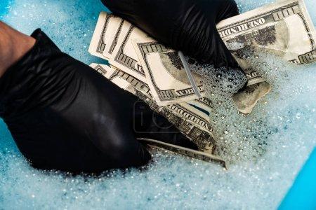 Photo pour Vue recadrée de l'homme dans les gants en caoutchouc noirs lavant des billets de banque de dollar dans des bulles de savon avec l'eau - image libre de droit