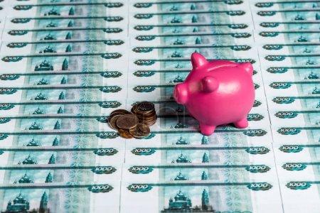 Photo pour Tirelire rose près des pièces métalliques sur l'argent russe - image libre de droit