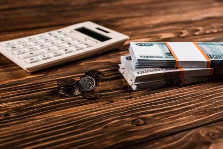 Photo for Selective focus of white calculator near russian money and coins on wooden table - Royalty Free Image