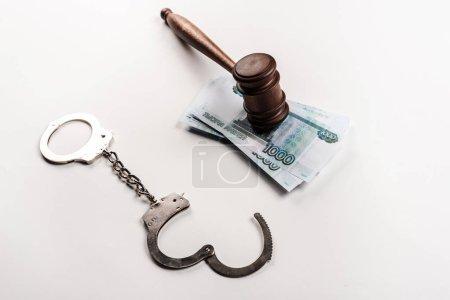 Photo pour Vue aérienne de marteau en bois sur l'argent russe près des menottes sur le blanc - image libre de droit