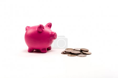 Photo pour Tirelire rose près des pièces d'argent et d'or sur le blanc - image libre de droit