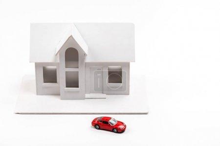 Photo pour Voiture rouge de jouet près de la maison de carton sur le blanc - image libre de droit
