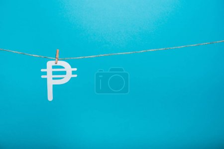 wooden cloth pin on line rope near russian money sign on blue