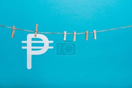 Photo pour Épingles en tissu en bois sur corde de ligne près de signe d'argent russe sur bleu - image libre de droit