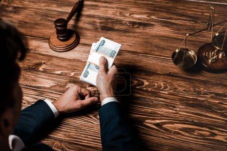 Photo pour Vue au-dessus du juge tenant le pot-de-vin près du marteau en bois - image libre de droit