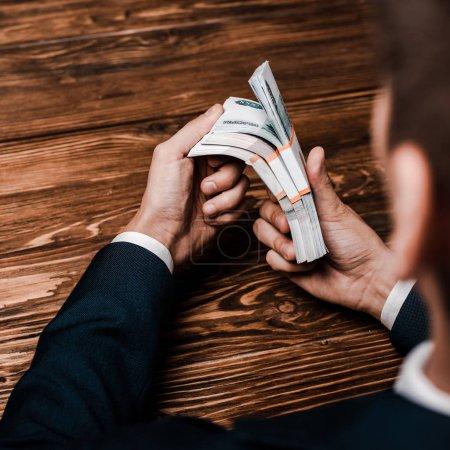 Photo pour Foyer sélectif de l'homme tenant l'argent russe près de la table en bois - image libre de droit