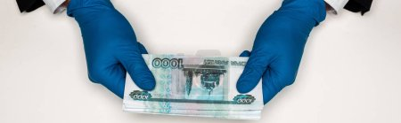 panoramic shot of man in blue latex gloves holding russian money on white