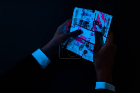 Photo for Cropped view of man holding russian money under uv lighting isolated on black - Royalty Free Image