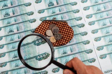 Photo pour Foyer sélectif de l'homme retenant la loupe près des pièces de monnaie sur le portefeuille de plaid près de l'argent russe - image libre de droit
