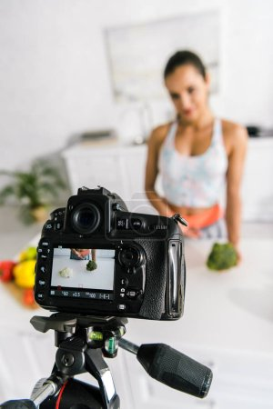 Photo for Selective focus of digital camera with sportswoman gesturing near vegetables - Royalty Free Image