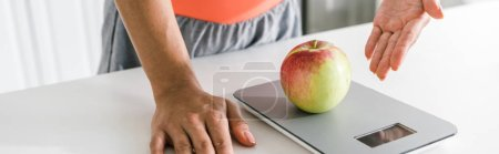 Photo for Panoramic shot of woman gesturing near food scales and apple - Royalty Free Image