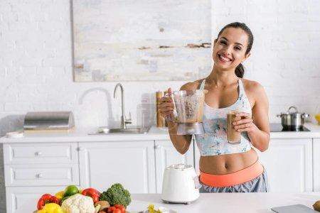 glückliche Frau hält Glas mit Smoothie in der Nähe von Gemüse