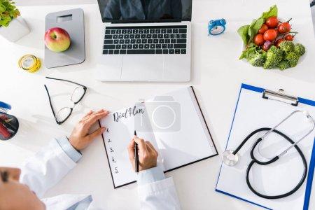 Photo pour Vue aérienne de l'écriture de nutritionniste dans le cahier près de l'ordinateur portatif - image libre de droit