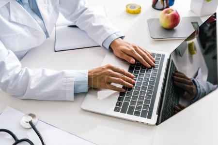 Photo for Cropped view of doctor typing on laptop with blank screen - Royalty Free Image