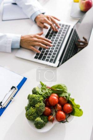 Photo pour Vue recadrée de nutritionniste tapant sur l'ordinateur portatif près du presse-papiers et des légumes - image libre de droit