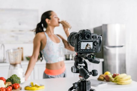 Photo for Selective focus of digital camera with girl drinking smoothie near fruits and vegetables on screen - Royalty Free Image