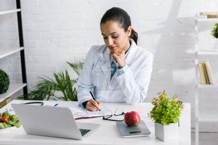 Photo for Attractive woman in white coat writing in notebook near laptop and vegetables - Royalty Free Image