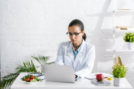 Photo for Attractive nutritionist in glasses using laptop near vegetables and plants - Royalty Free Image