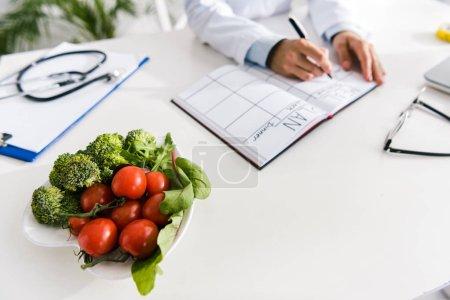 Photo pour Vue recadrée de l'écriture de nutritionniste dans le cahier avec le plan de repas près des légumes - image libre de droit