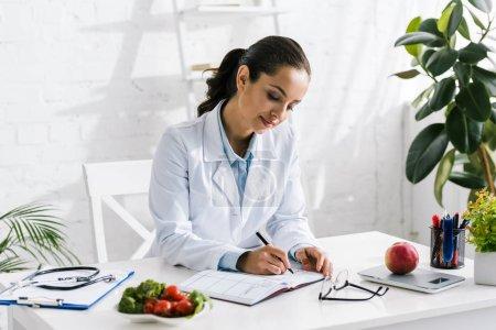 Photo pour Attrayant jeune nutritionniste en manteau blanc écrit dans un cahier - image libre de droit