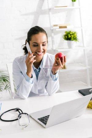 Photo pour Nutritionniste joyeux parlant sur smartphone et tenant pomme à la clinique - image libre de droit