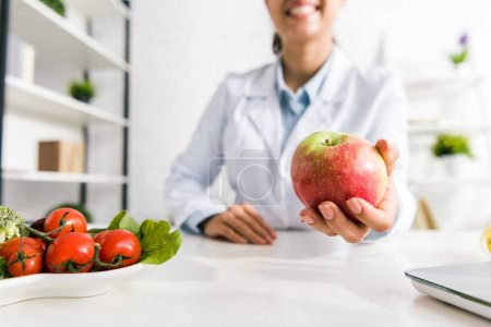 Photo for Cropped view of nutritionist holding tasty apple near vegetables - Royalty Free Image