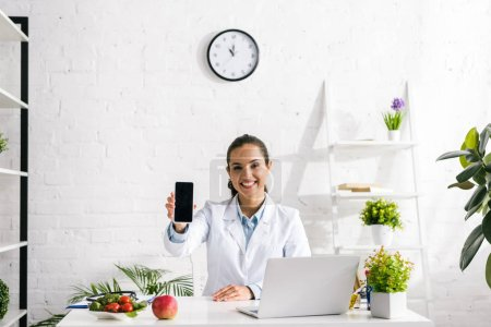 Photo pour Heureux nutritionniste tenant smartphone avec écran vide près de l'ordinateur portable - image libre de droit
