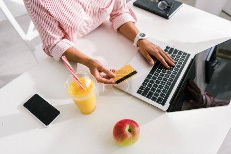 Photo pour Vue aérienne de la femme retenant la carte de crédit près de l'ordinateur portatif et du smartphone avec des écrans vides - image libre de droit
