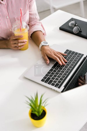 Photo pour Vue recadrée de fille utilisant l'ordinateur portatif tout en retenant la tasse en plastique avec le jus d'orange - image libre de droit